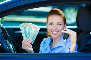 Red head holding keys and cash from her car window because of title loan